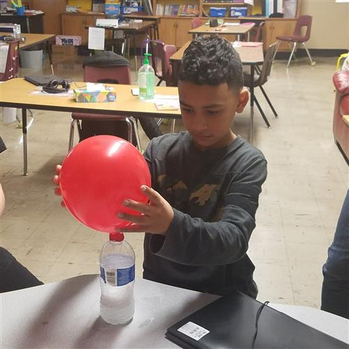 Student engaged in learning activity with balloon