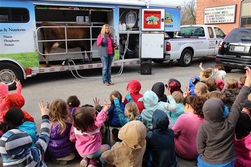 Students are visited by a cow to learn about dairy farming and nutrition