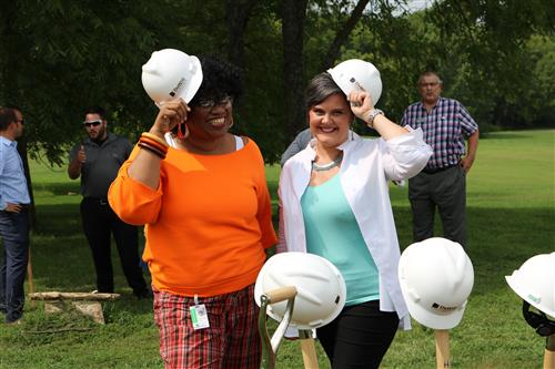 Two community leaders where hard hats at groundbreaking