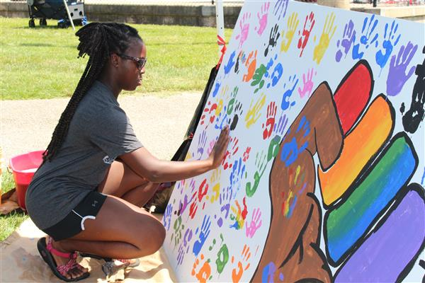 Girl adds handprint to sign at Juneteenth