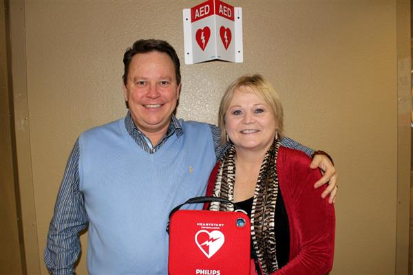 Wellness Coordinator Jeff Rogers and Jean Grabeel stand in front of AED case.