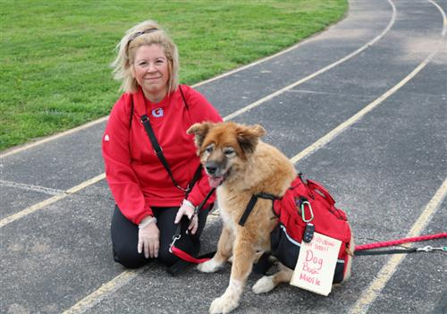Nicole Bueno and her dog, Honey, wearing a backpack